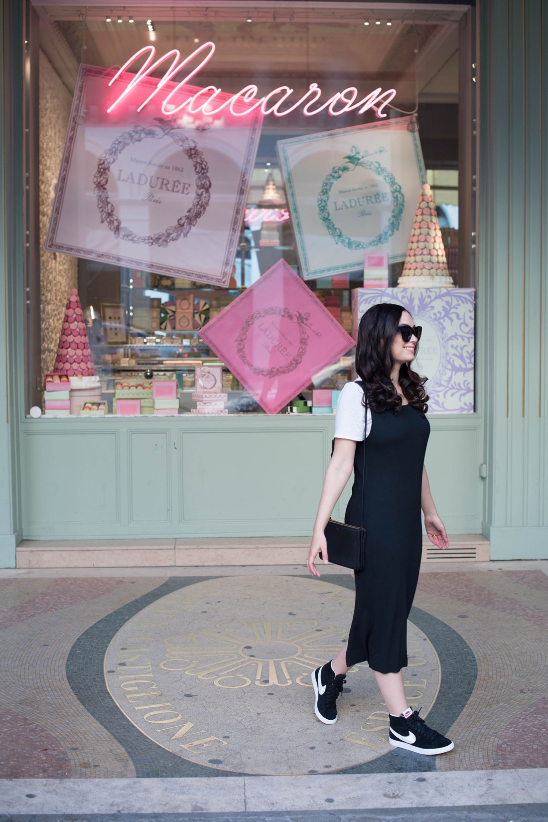 Photo of lifestyle blogger Cee Fardoe at Laduree in Paris, wearing a black pinafore dress and Nike sneakers