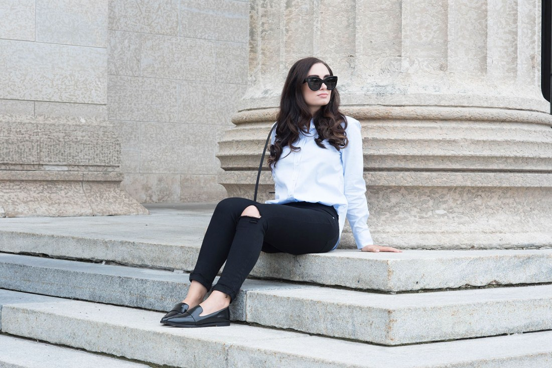 Canadian fashion blogger Cee Fardoe of Coco & Vera sits on the steps of the Manitoba legislature wearing Celine Audrey sunglasses and Paige jeans