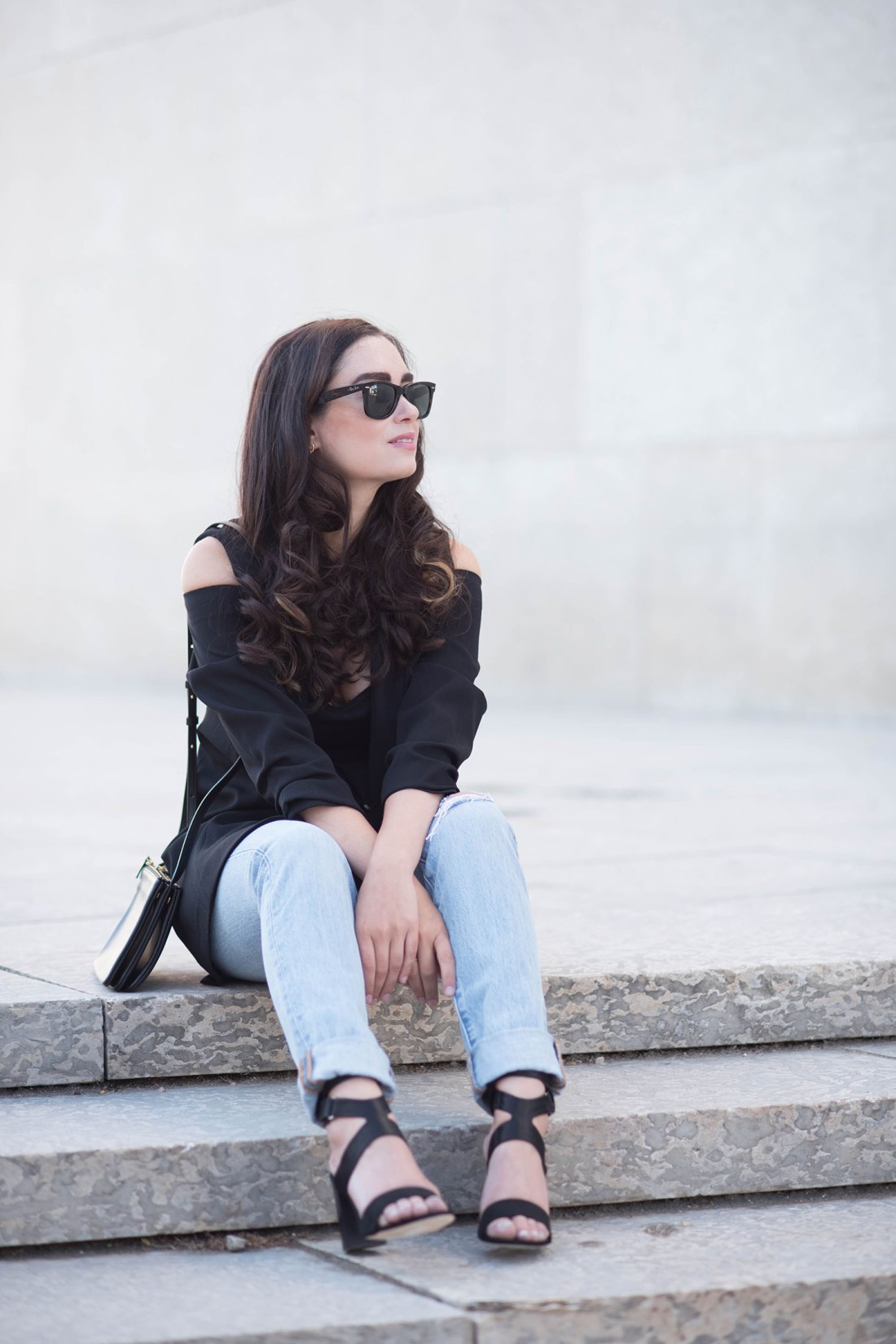 Fashion blogger Cee Fardoe of Coco & Vera sits on the stairs wearing an Ever New cold shoulder coat and Levis jeans