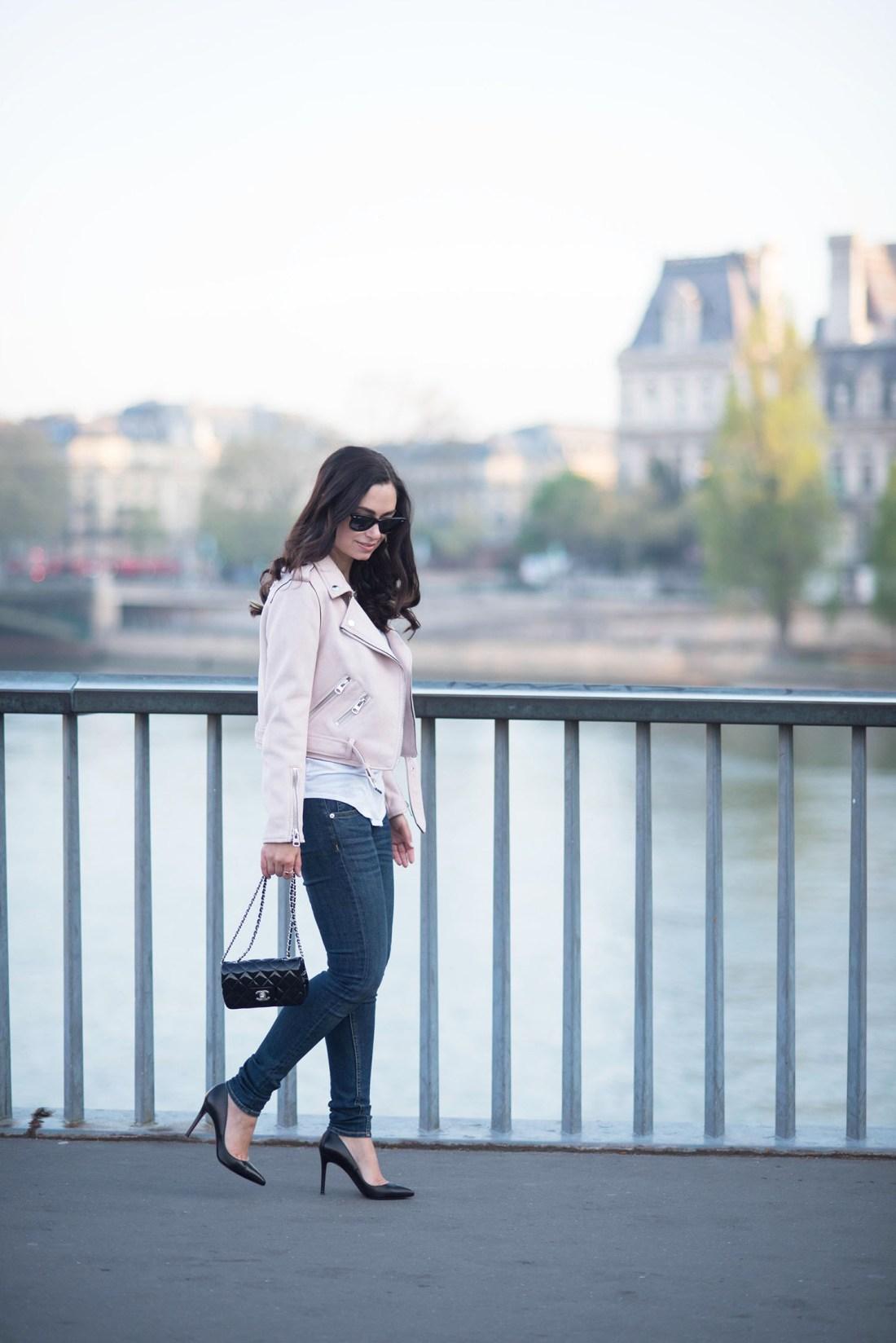 Fashion blogger Cee Fardoe of Coco & Vera walks in front of Hotel de Ville in Paris wearing a Zara pink moto jacket