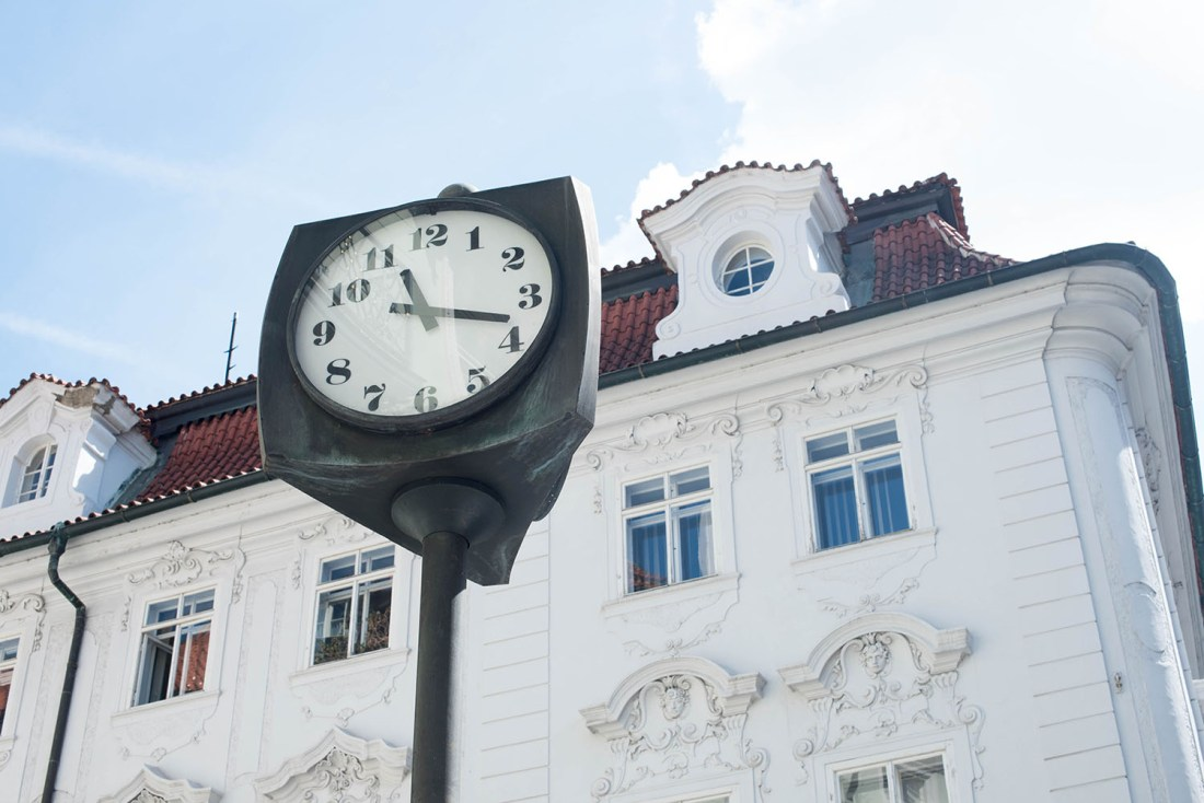 A white building and vintage clock in Prague, captured by travel blogger Cee Fardoe of Coco & Vera