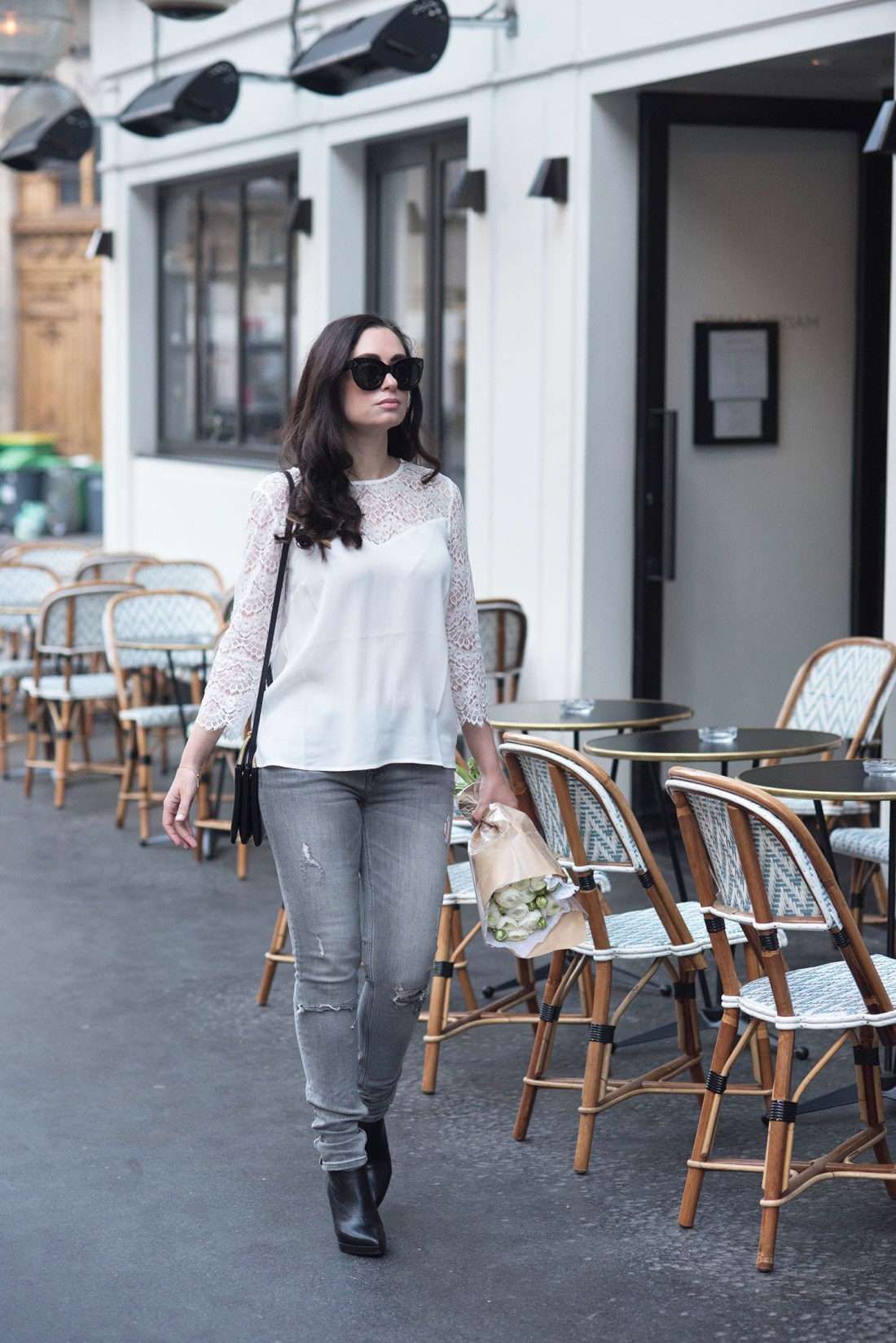 Fashion blogger Cee Fardoe of Coco & Vera walks on the street in Paris carrying a Celine trio bag and wearing Zara grey jeans