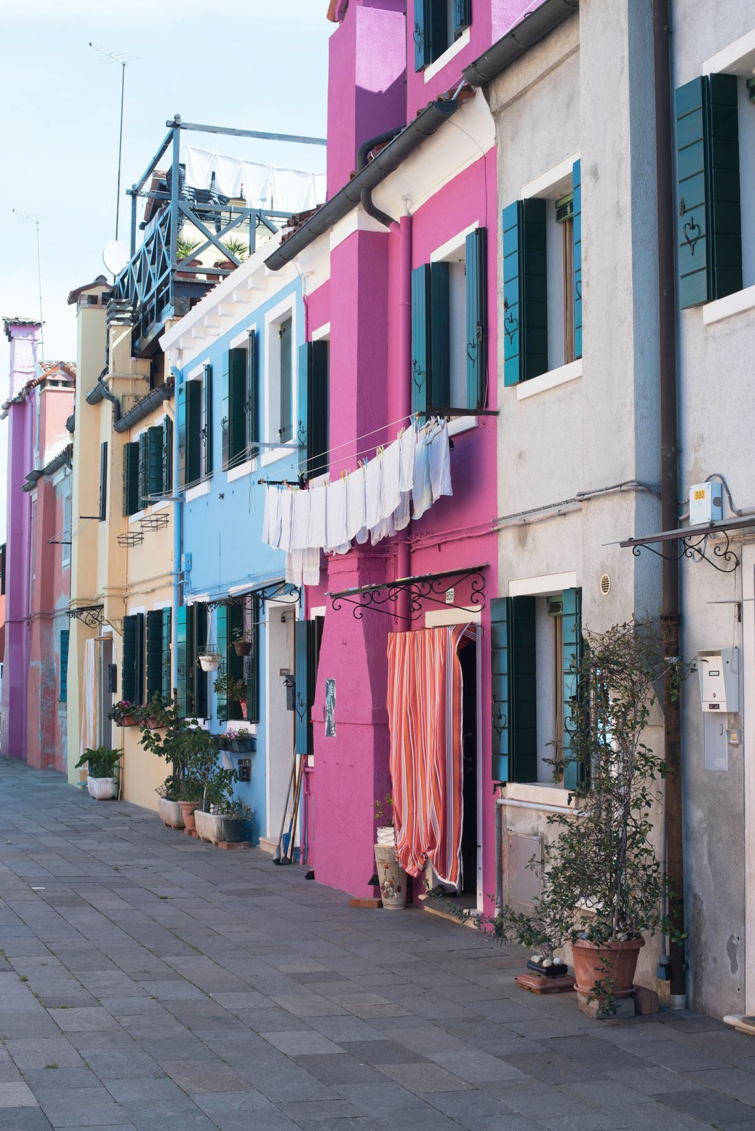 Pink and blue houses in a narrow laneway on Burano, Italy, captured by travel blogger Cee Fardoe of Coco & Vera