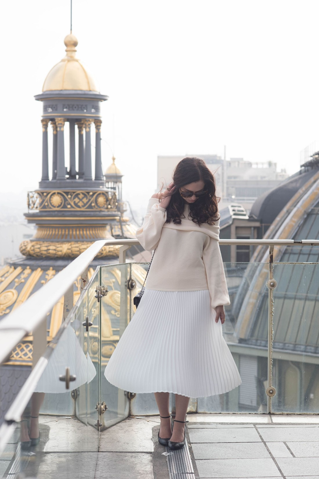Fashion blogger Cee Fardoe of Coco & Vera stands on the rooftop of Paris department store Printemps wearing a Zara blush sweater and Aritzia pleated skirt