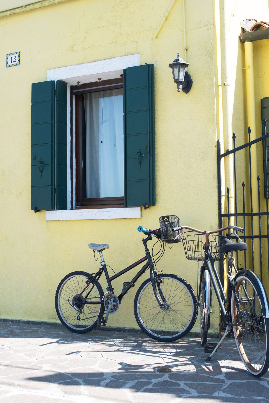Two bicycles lean against a yellow house on the island of Mazzorabo in the Venetian Lagoon, captured by travel blogger Cee Fardoe of Coco & Vera