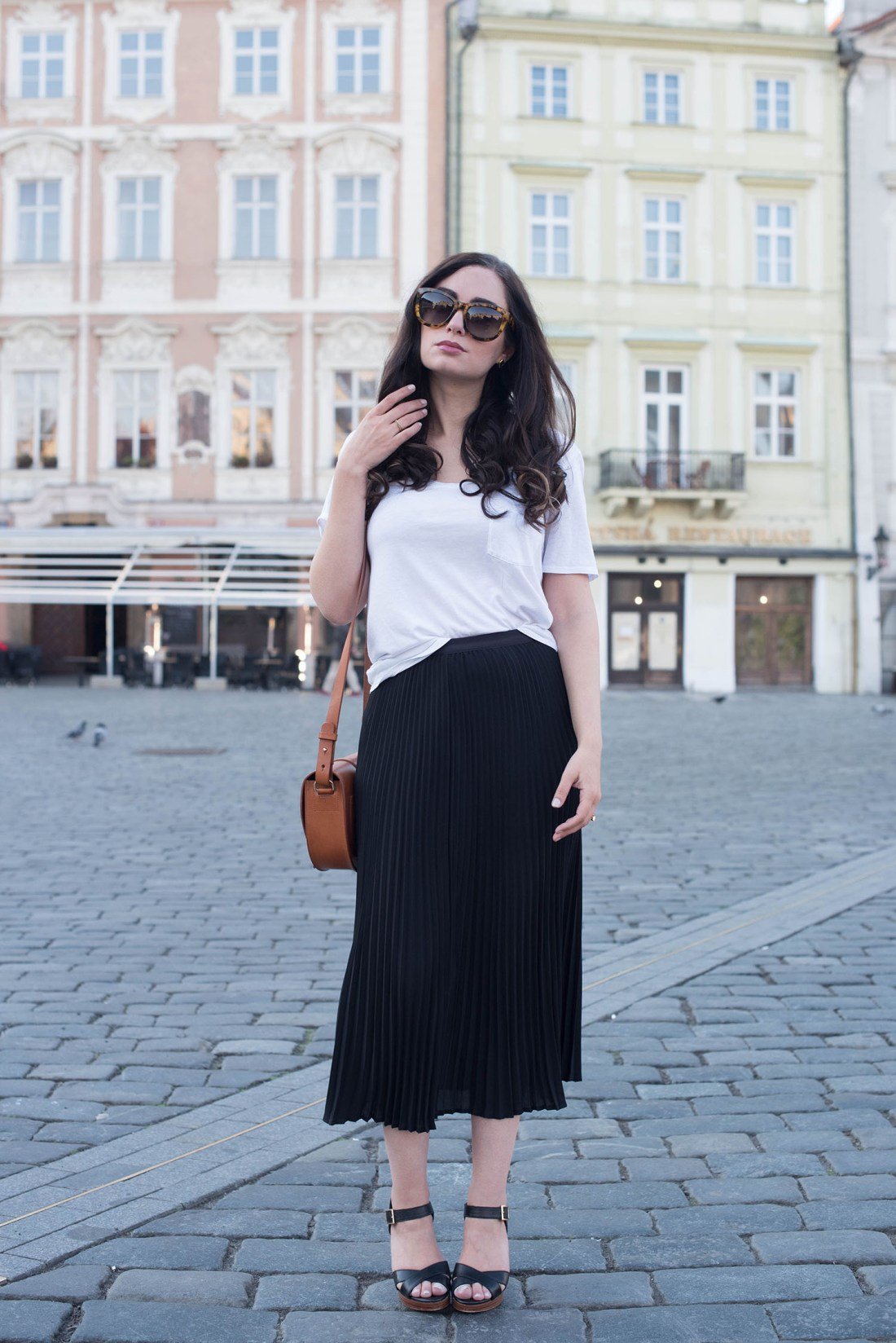 Fashion blogger Cee Fardoe of Coco & Vera stands at Old Town Square in Prague wearing a black pleated Aritzia skirt and Le Chateau sandals