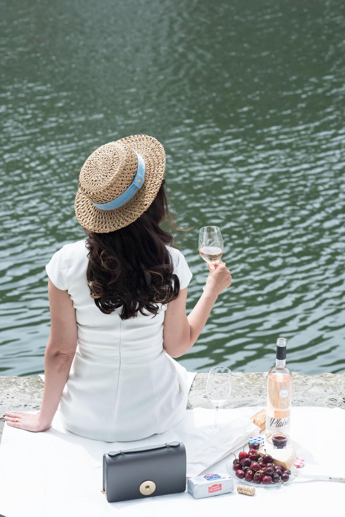 Fashion blogger Cee Fardoe of Coco & Vera celebrates Bastille Day in Paris drinking rose on the Seine wearing a Krasnova Modiste hat