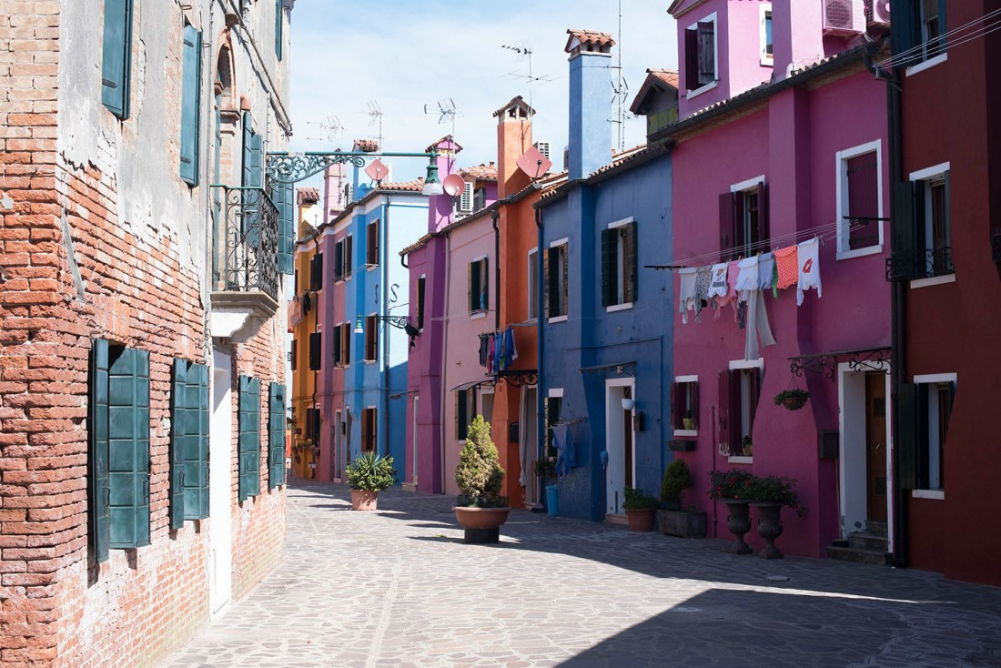 A narrow lane of brightly coloured houses on Burano, Italy, as captured by travel blogger Cee Fardoe of Coco & Vera