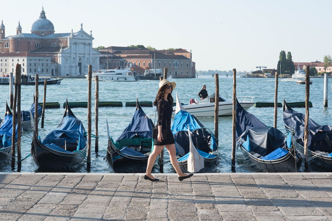 Canadian fashion blogger Cee Fardoe of Coco & Vera walks along the Grand Canal in Venice wearing Miumiu flats and Gentlefawn lace dress, carrying a Celine trio bag