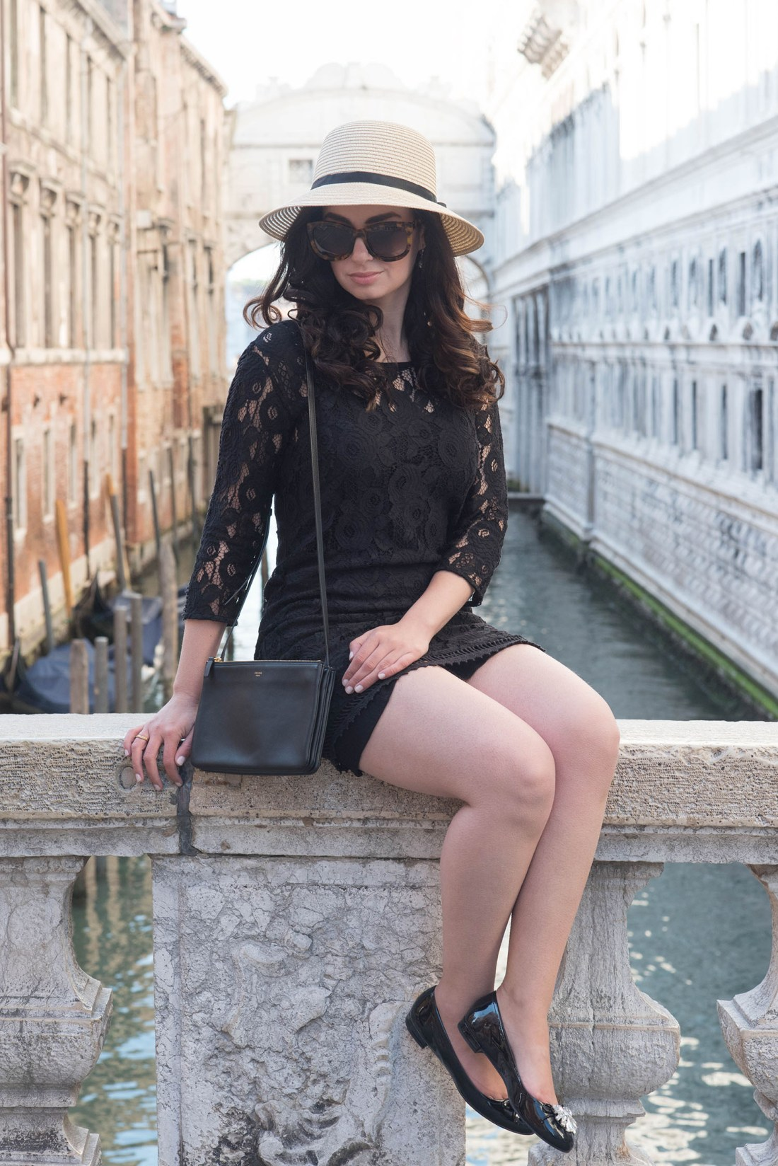 Fashion blogger Cee Fardoe of Coco & Vera sits on a bridge in Venice wearing a Gentlefawn lace dress, Miumiu bejewelled flats, Anine Bing Los Angeles sunglasses and carrying a Celine trio bag