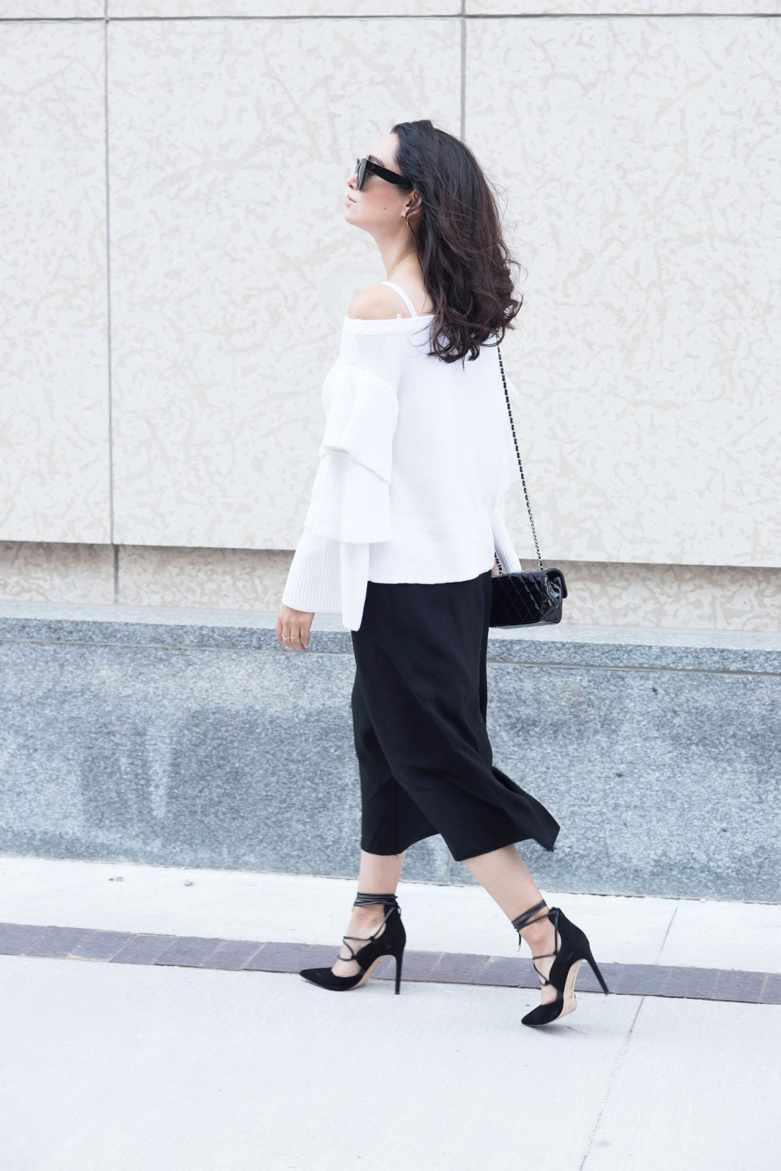 Fashion blogger Cee Fardoe of Coco & Vera walks in downtown Winnipeg wearing a white endless rose sweater and Same Edelman lace-up heels