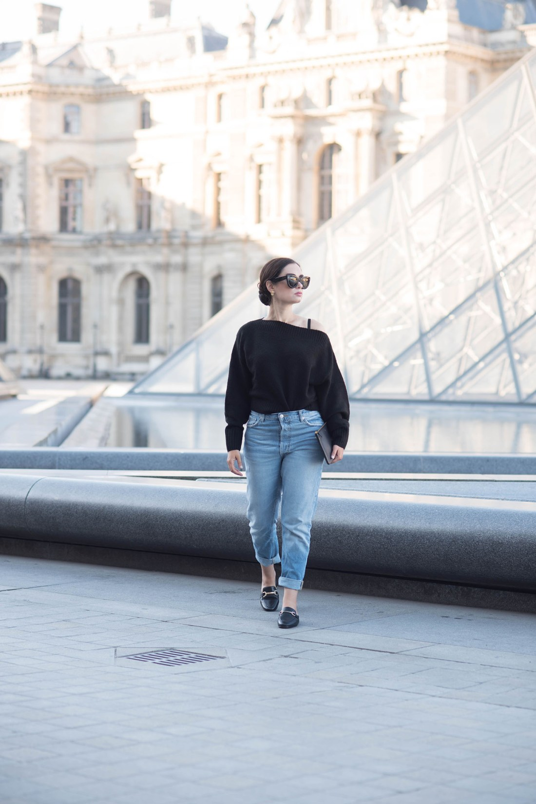 Fashion blogger Cee Fardoe of Coco & Vera walks in front of the Louvre pyramid wearing Zara boyfriend jeans and carrying a Celine clutch