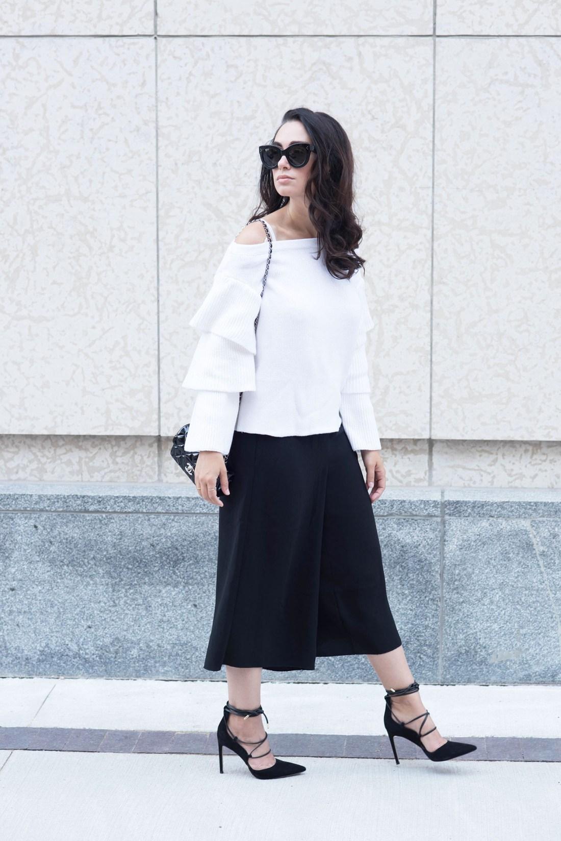 Winnipeg fashion blogger Cee Fardoe of Coco & Vera wears a white off-shoulder sweater, Aritzia black culottes and Sam Edelman lace-up heels
