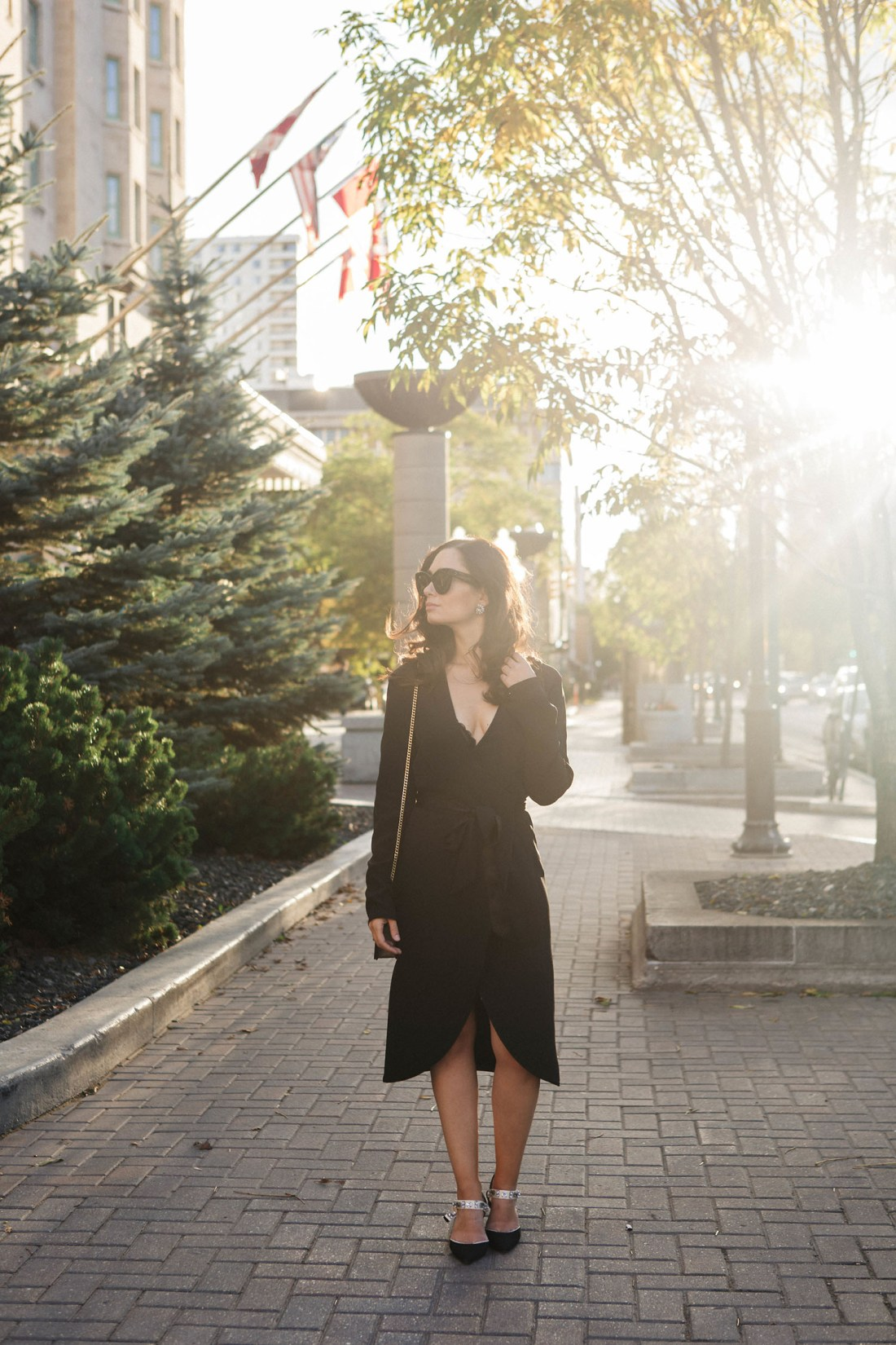 Fashion blogger Cee Fardoe of Coco & Vera stands at the Fort Garry Hotel in Winnipeg wearing a black silk wrap dress and Zara bejewelled slingback pumps, photographed by Christa Wong Photography