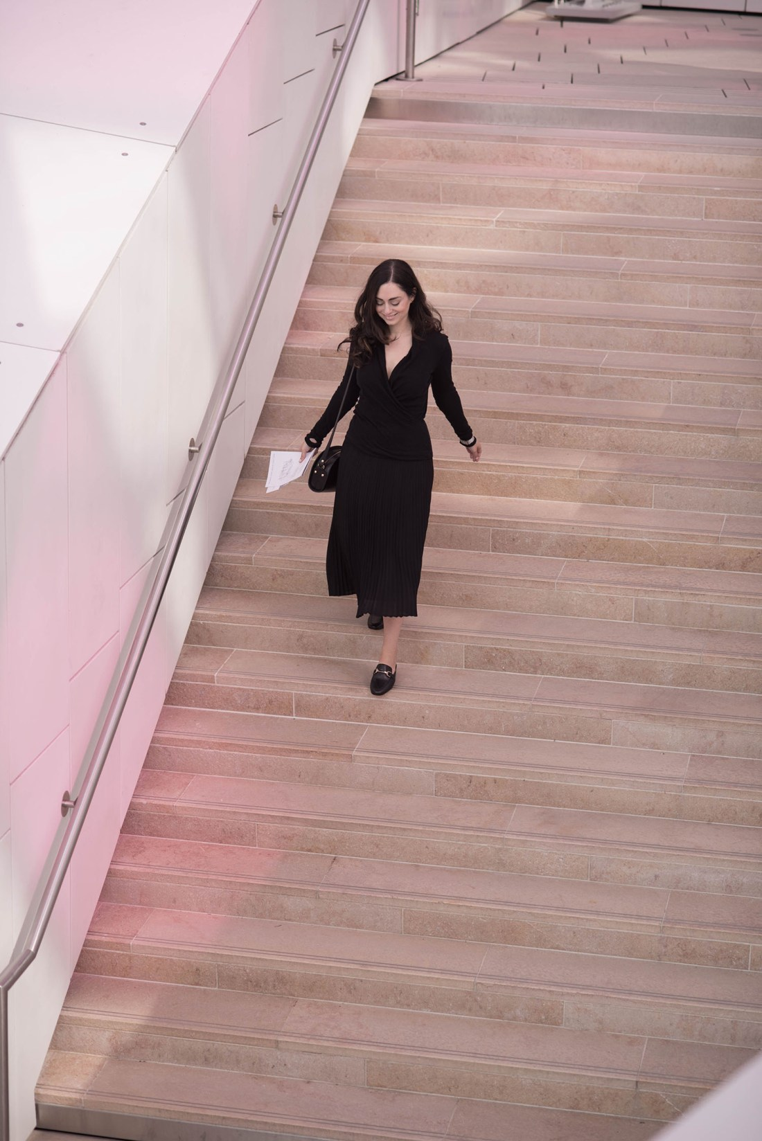 Fashion blogger Cee Fardoe of Coco & Vera walks down the stairs at the Fondation Louis Vuitton in Paris wearing an Aritzia pleated skirt and an Enza Costa wrap top