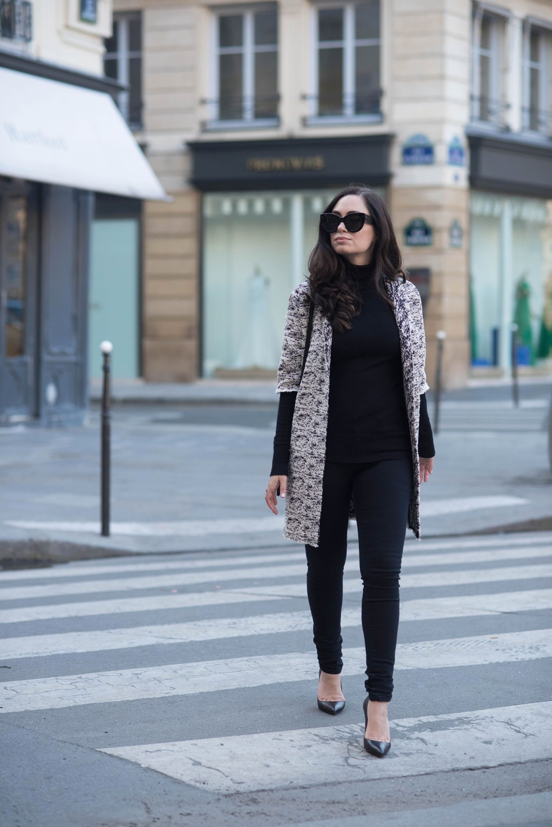 Fashion blogger Cee Fardoe of Coco & Vera walks at Place des Victoires in Paris wearing a Floriane Fosso coat and Christian Louboutin Pigalle pumps
