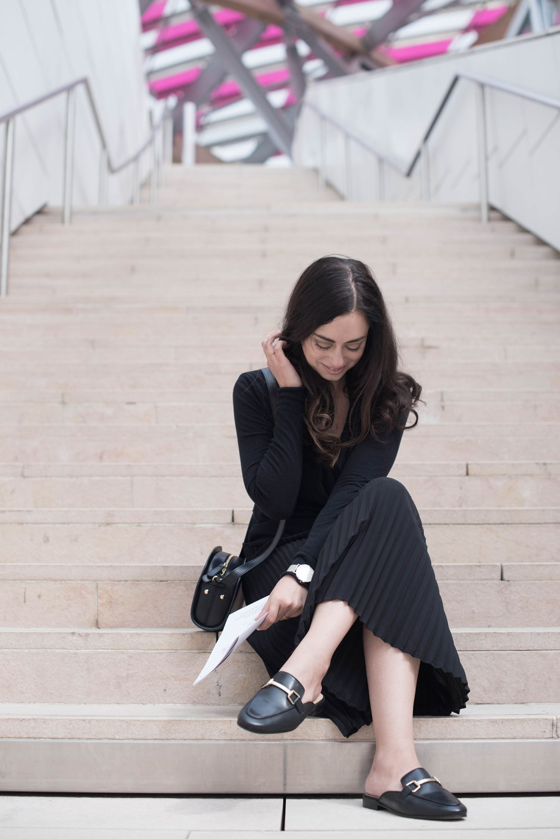 Fashion blogger Cee Fardoe of Coco & Vera sits on the stairs at the Fondation Louis Vuitton wearing an Aritzia pleated skirt and Jonak mules