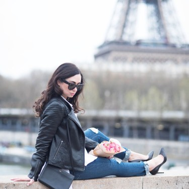 Fashion blogger Cee Fardoe of Coco & Vera sits near the Eiffel Tower in Paris wearing Christian Louboutin Pigalle pumps and Paige Hoxton jeans