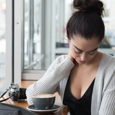 Portrait of fashion blogger Cee Fardoe of Coco & Vera at Fools & Horses coffee shop in Winnipeg wearing a grey ribbed cardigan from Gap and a black silk tank from Aritzia