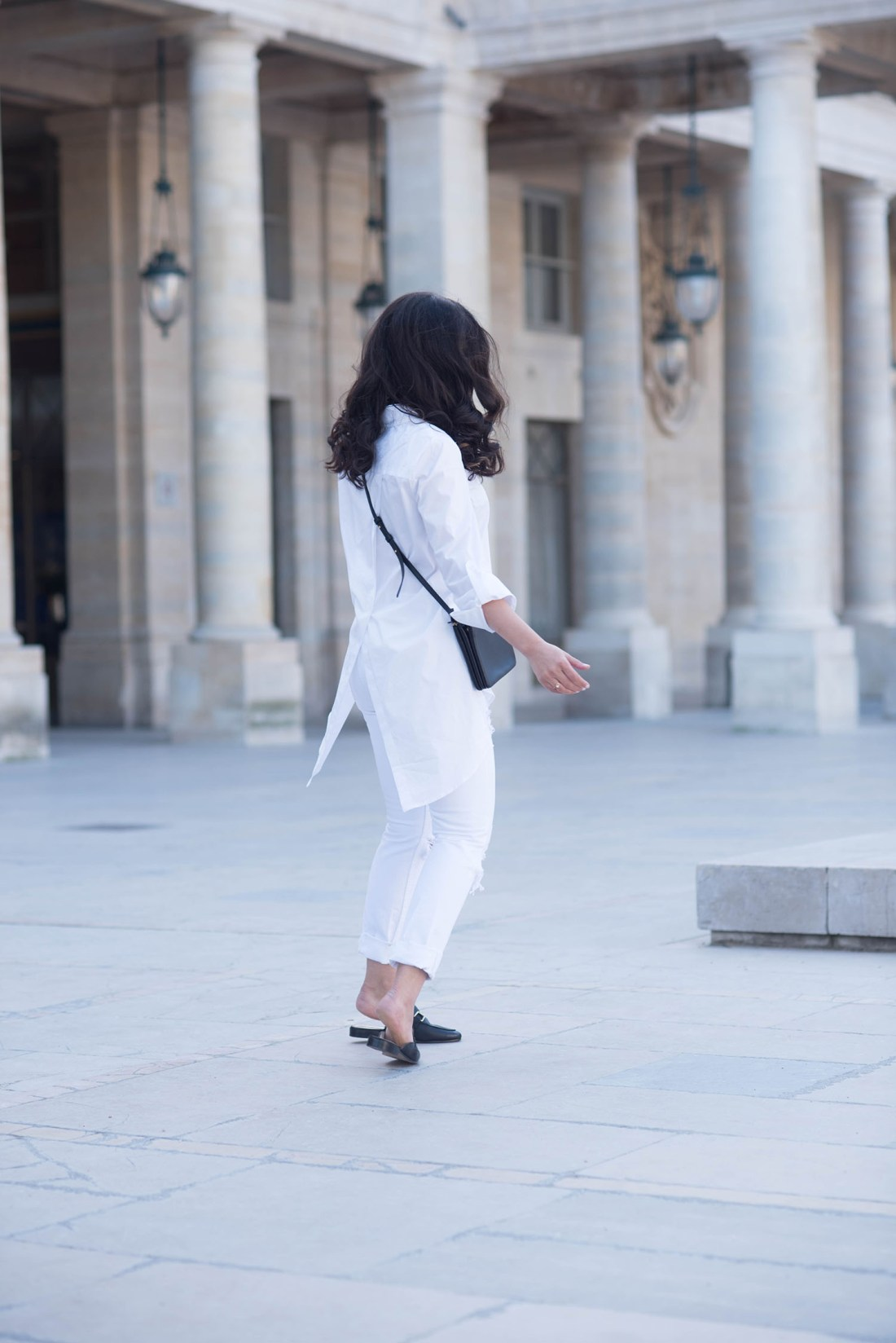 Canadian fashion blogger Cee Fardoe of Coco & Vera twirls in the Palais Royal, wearing Jonak mules and a Marled white blouse