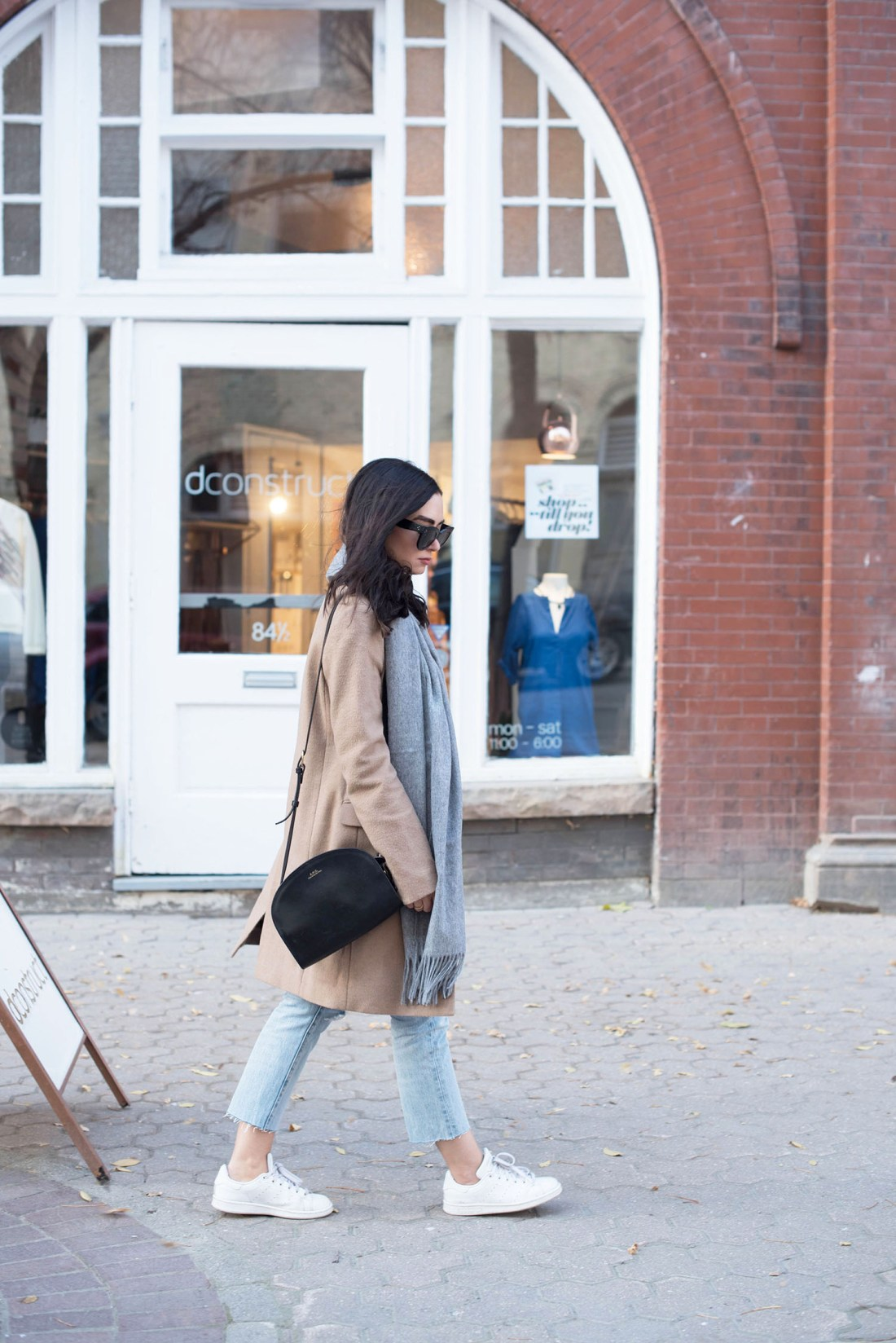 Winnipeg fashion blogger Cee Fardoe of Coco & Vera walks the streets of The Exchange District wearing a Uniqlo camel coat and carrying an APC half moon bag