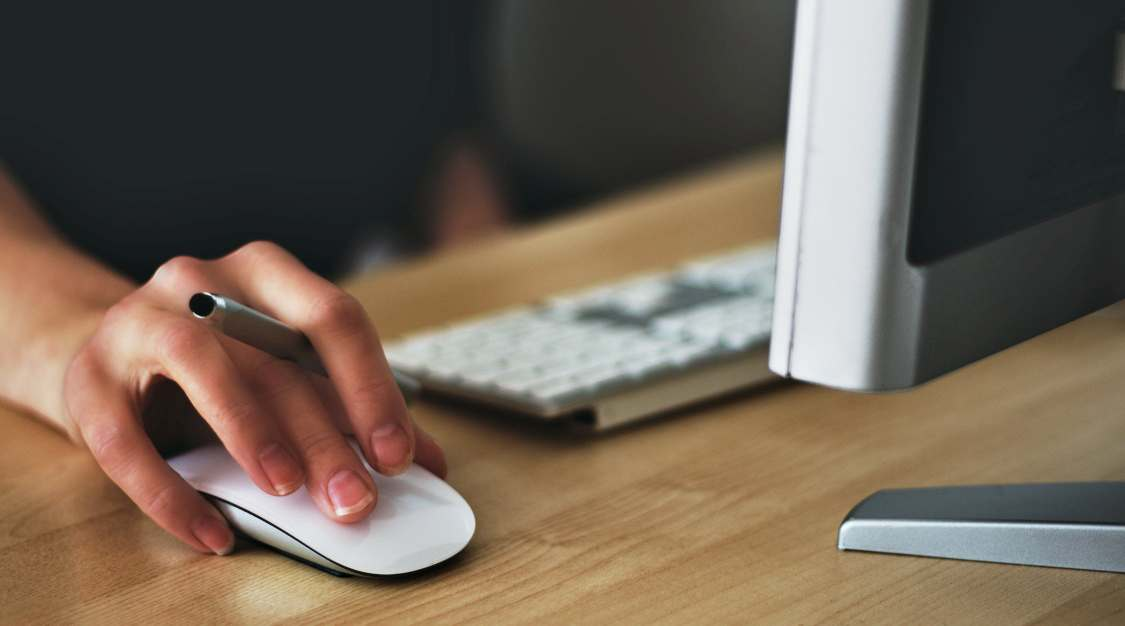 A person's hand holding a white mouse on a wooden desk