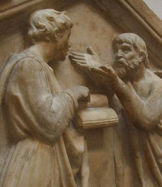 Relief of men reasoning over a book