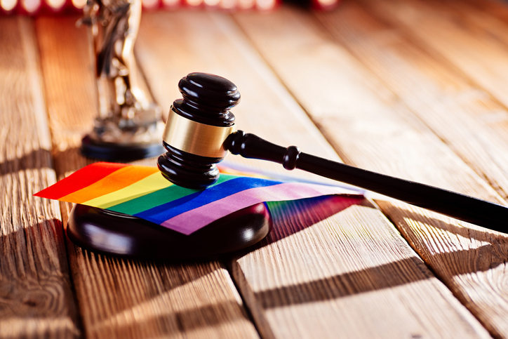 Judge wooden mallet - symbol of law and justice with lgbt rainbow colours flag. Lgbt rights and law