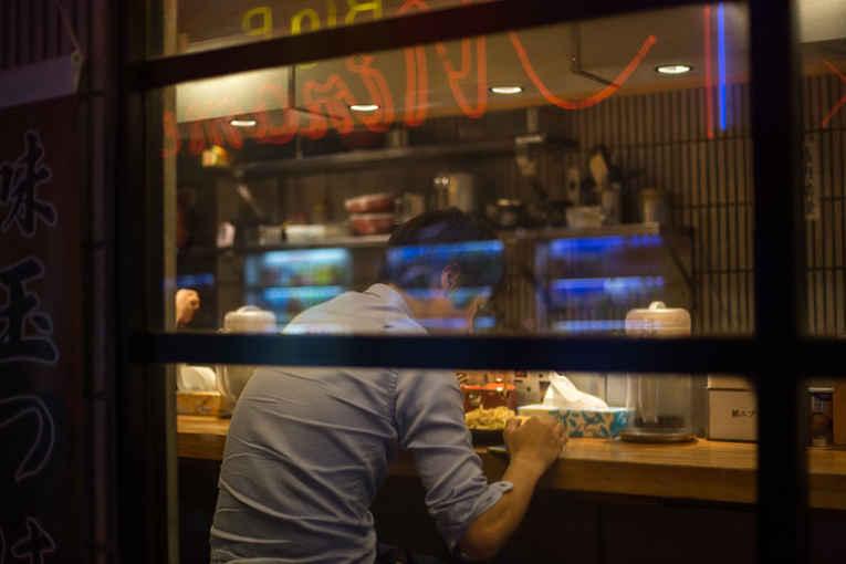 Homem comendo sozinho no Japão