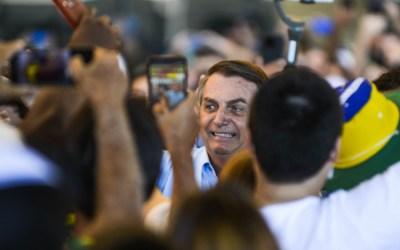 Bolsonaro entra de surpresa em avião, ganha abraços, mas é xingado por opositores