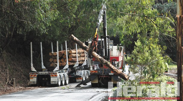 Log truck rolls over on notorious corner