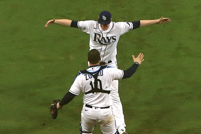 SAN DIEGO, CALIFORNIA - OCTOBER 17: Peter Fairbanks #29 and Mike Zunino #10 of the Tampa Bay Rays celebrate a 4-2 win against the Houston Astros to win the American League Championship Series at PETCO Park on October 17, 2020 in San Diego, California. Sean M. Haffey/Getty Images/AFP