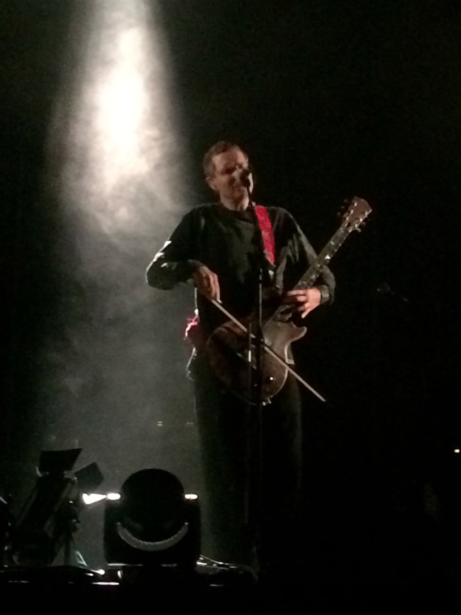 photo of JOnsi from Sigur ros singing and bowing guitar