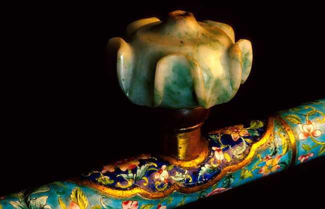 A close-up of an opium pipe of featuring Canton enamel and a jade bowl.
