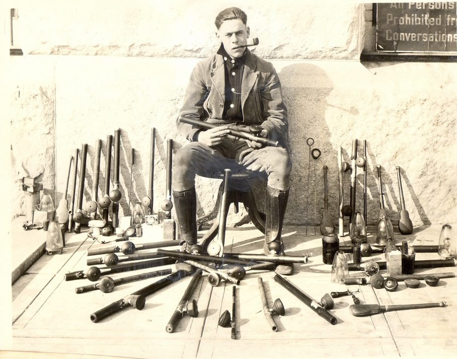 A police officer poses with opium pipes, opium lamps, and other paraphernalia confiscated at opium den raids in San Francisco.