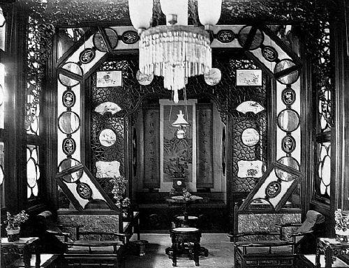 "A luxurious and ornately decorated opium smoking room, possibly inside one of the ""flower boat"" that could be hired for a night of opium smoking on the Pearl River. The opium bed is at the back of the room. Circa 1880."