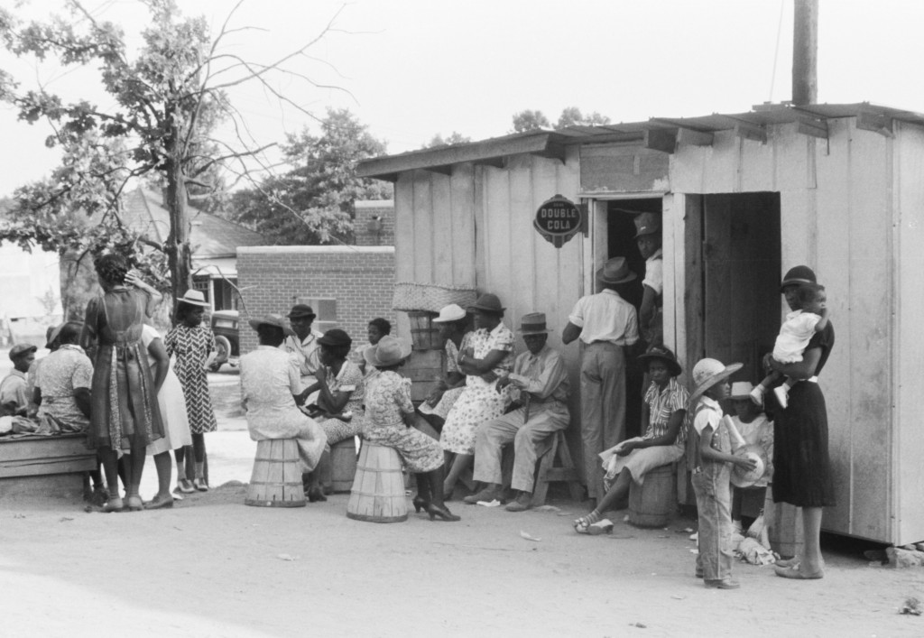 A crowd gathers outside a store and barbershop in Union Point, Georgia, circa 1941. Photo by Jack Delano, via the Library of Congress.