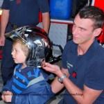 Sapeur Pompier demonstrating helmet on future rescuer recruit