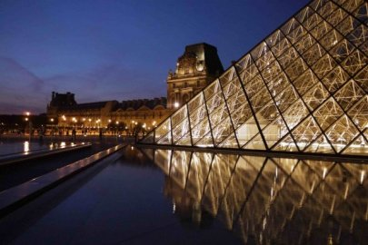 Diagonal evening view of pyramid, water, and north wing of Louvre