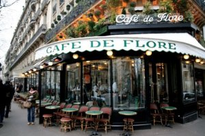 Café de Flore with tables arranged out front and a lady in a pink scarf