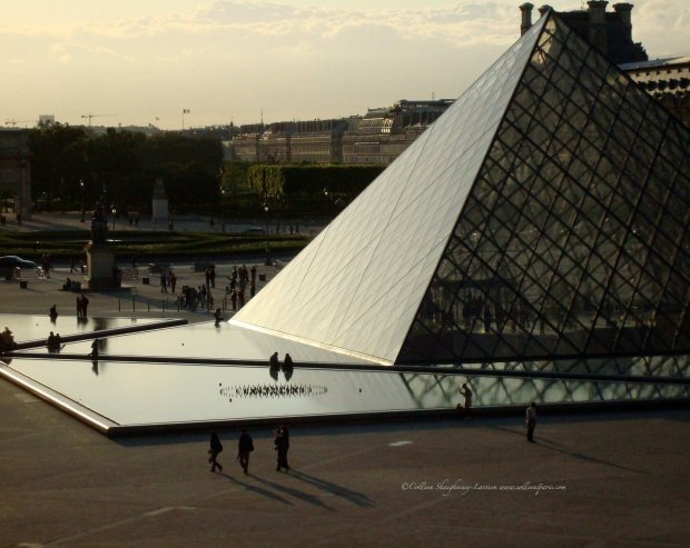 Late afternoon view of I. M. Pei's pyramid at the Louvre in paris with people walking and long shadows