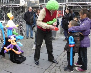 Balloon clown at Pompidou Centre signing balloons for two children