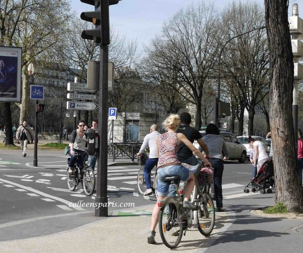 Bikes crosing street at bike crosswalk in Paris near Bastille and Canal Saint Martin
