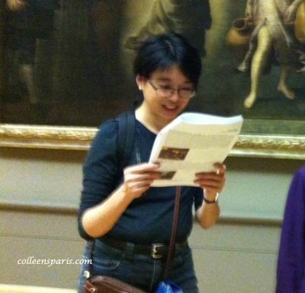 Woman looking at a map in the Louvre on ThatLou tour for the Paris le nez en l'air story
