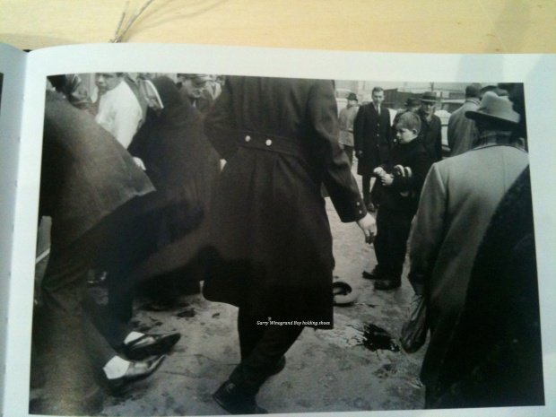Garry Winogrand Boy holding shoes