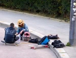 Girl wearing hat with her skateboard on Trocadero walkway toward Eiffel Tower
