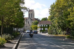 Auvers-sur-Oise motorcyle on street, church in background