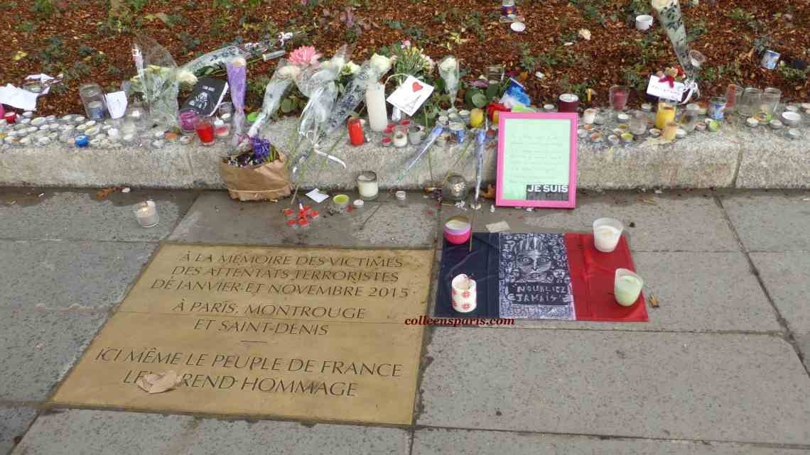 Plaque to victims of 2015 attacks Republique Monument in Paris with posters, notices, lost child, candles and flowers in Paris France
