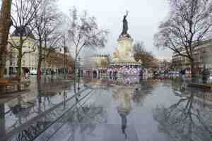 Republique Monument in Paris with posters, notices, lost child, candles and flowers in Paris France reflected in the pool of water from the rain
