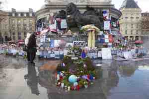 Couple looking at Republique Monument in Paris with posters, notices, lost child, candles and flowers in Paris France